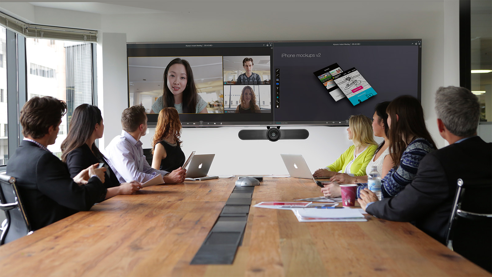 Team meeting in a conference room, with other employees on video conference