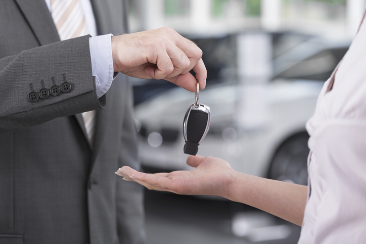Man in a suit handing car keys to someone else
