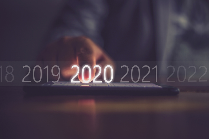 Illuminated 2020 sign, with a finger touching it