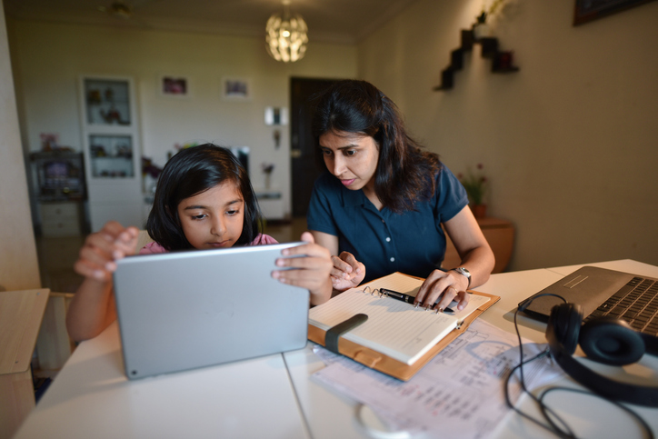 Mother looking at daughter's laptop during homeschooling lesson