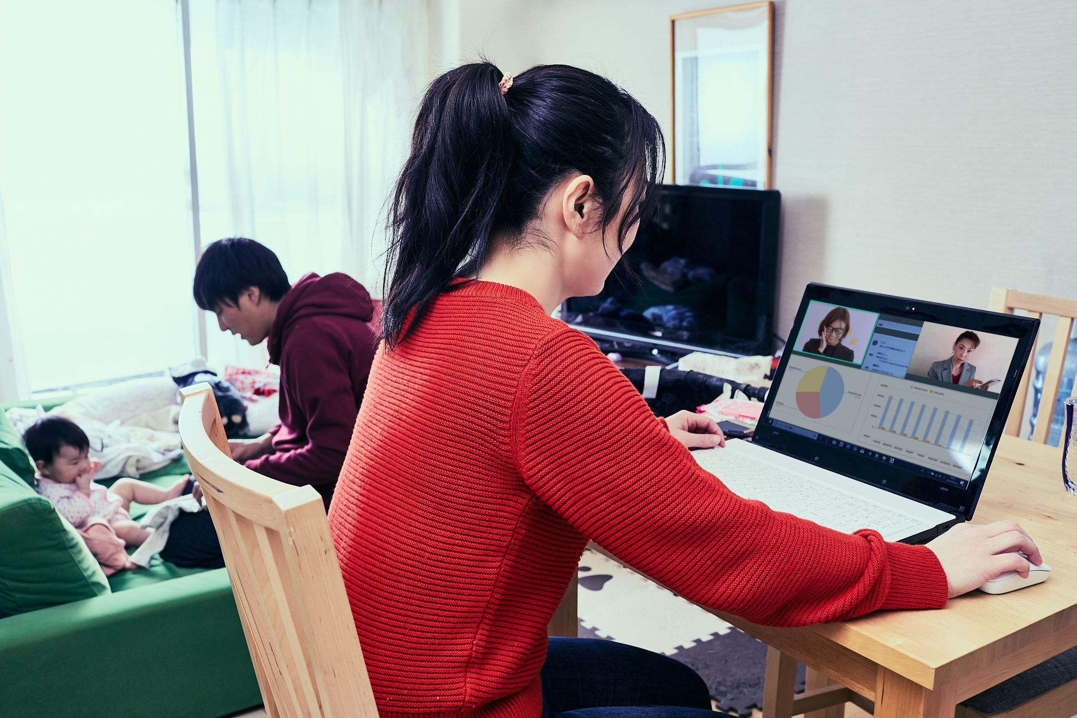 Woman on a video call with family in the background