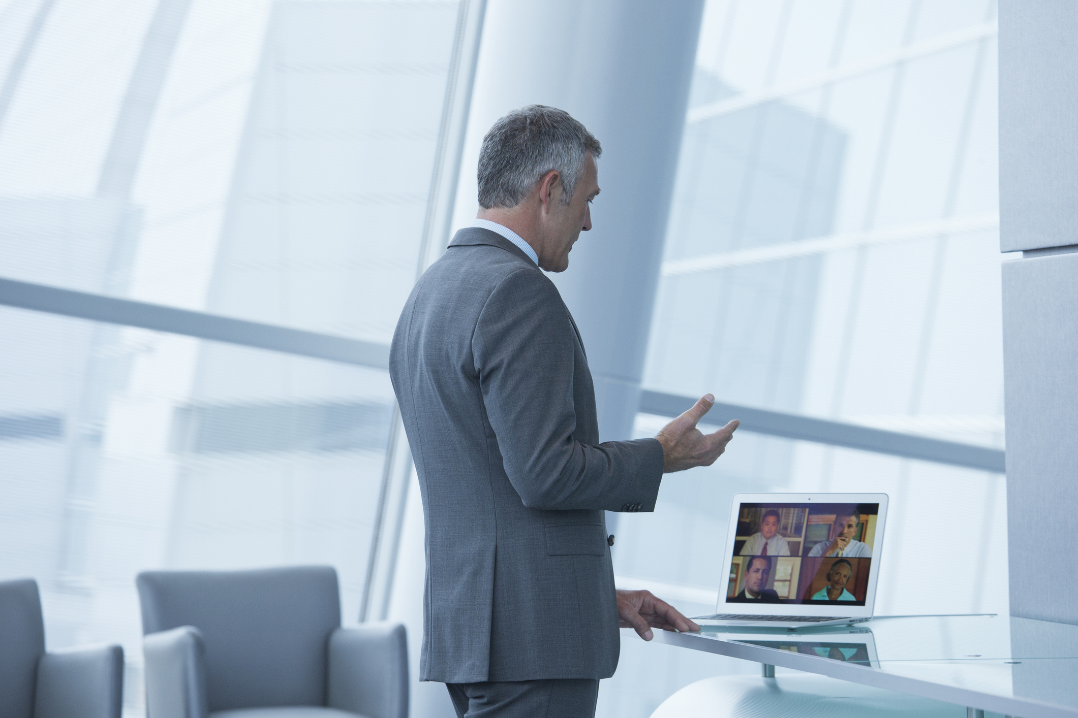 A CIO is standing in his office, talking on a video conference on his laptop