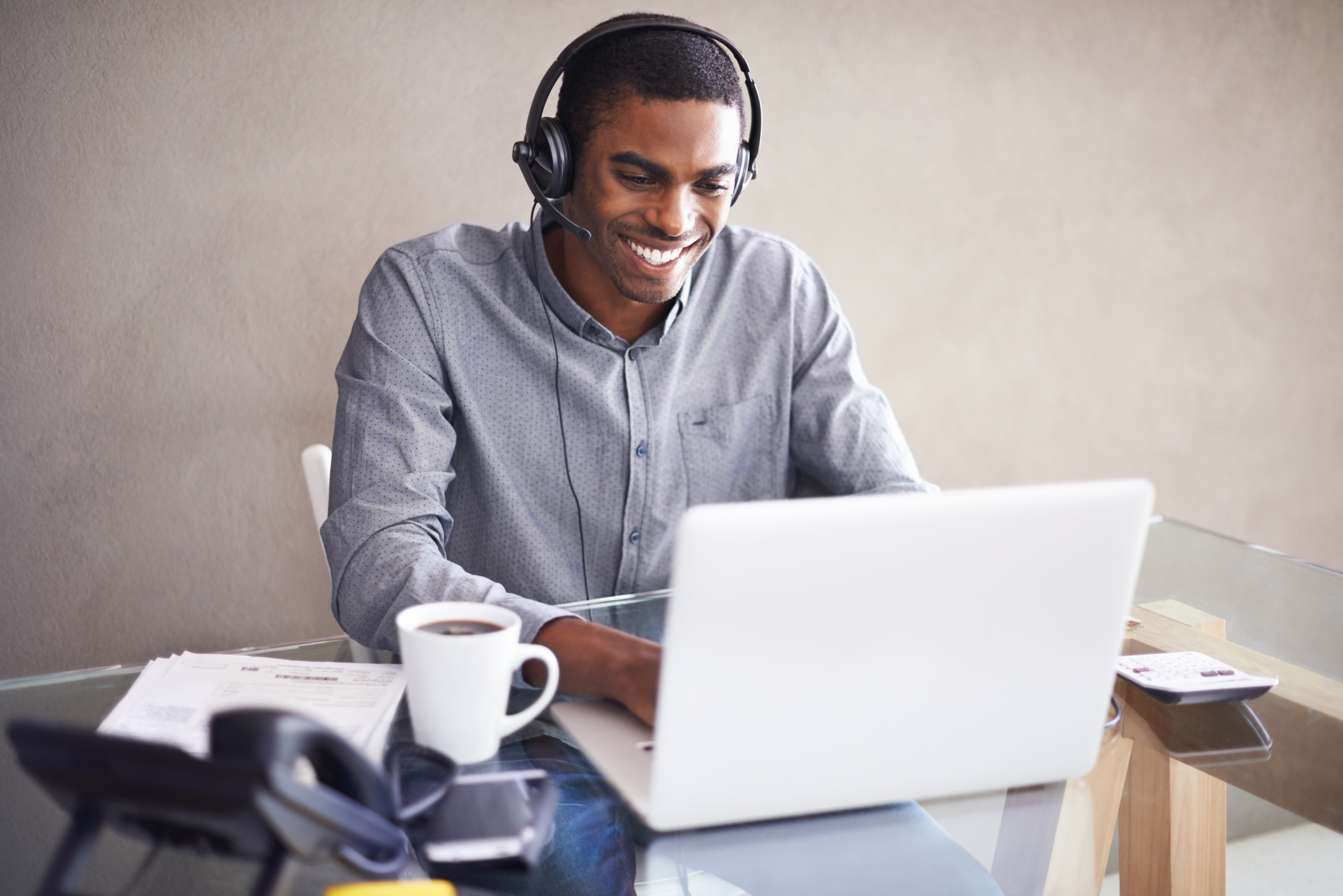 Man on his laptop with a headset on