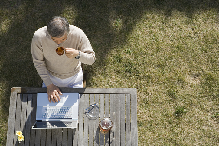 A man sits at a picnic table, sipping a drink and doing work on his laptop