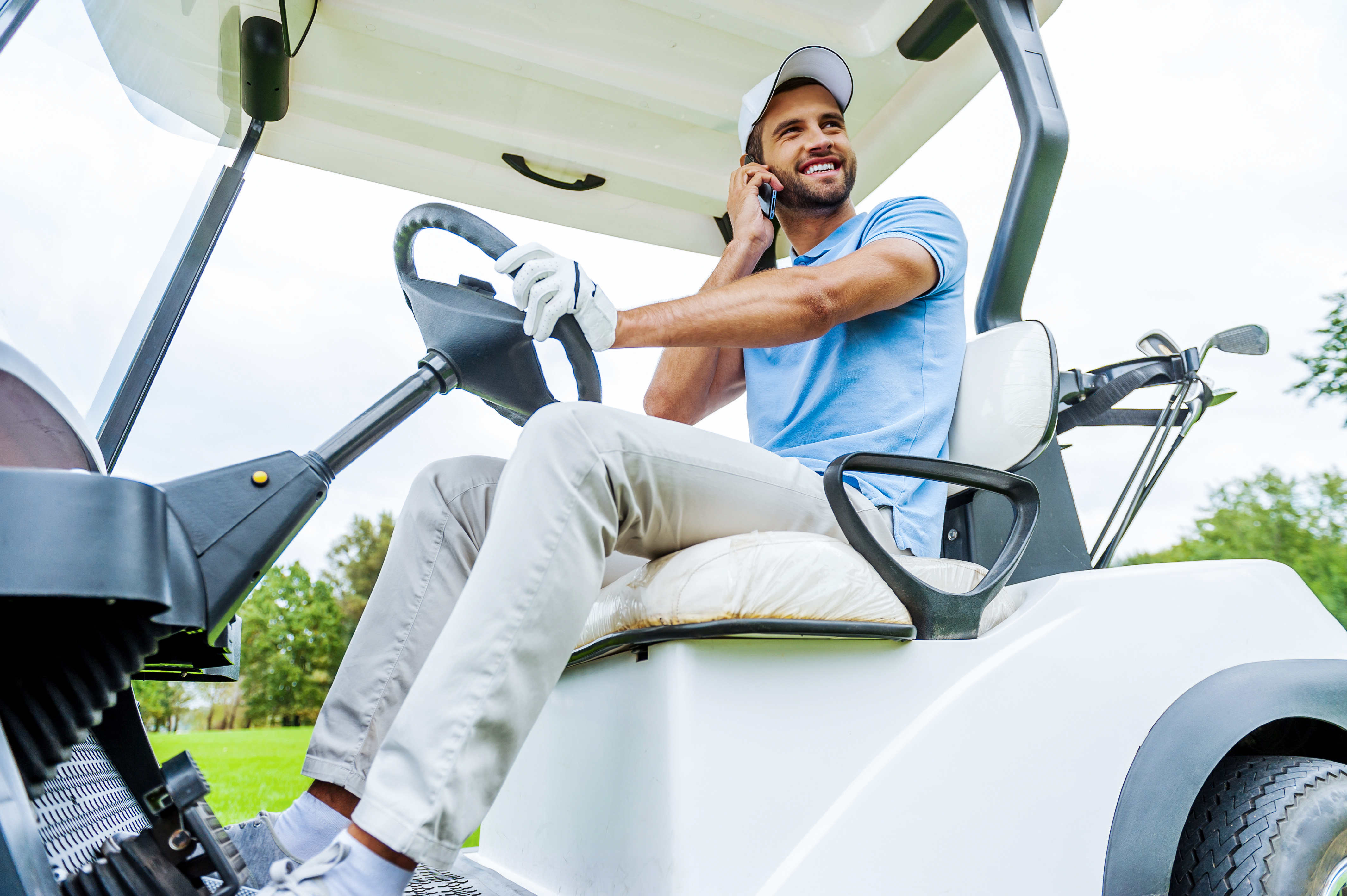 A golfer driving a golf cart and talking on his cell phone