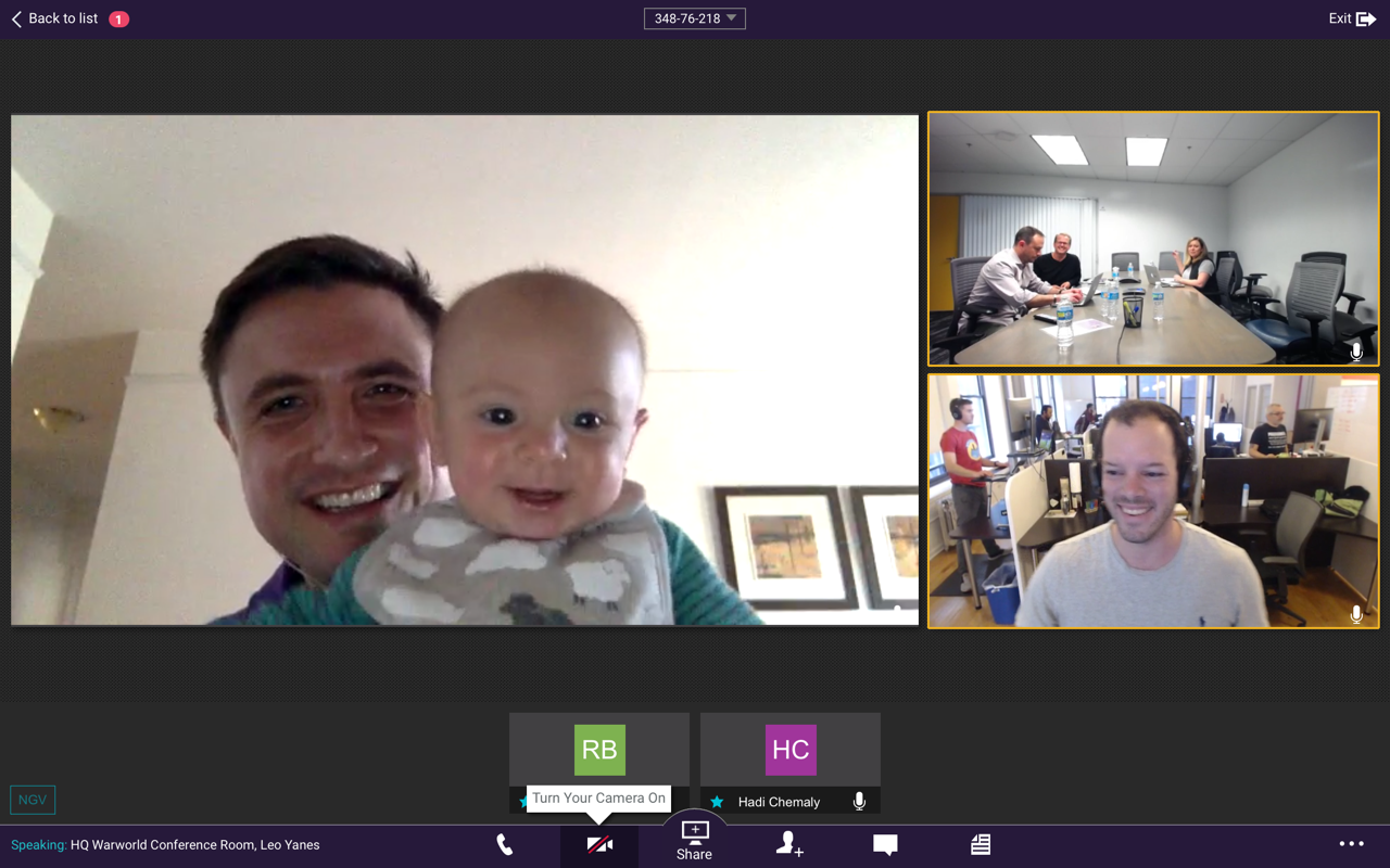 Screenshot of Fuze employees, with one holding up his baby to the screen; the others are in the office.