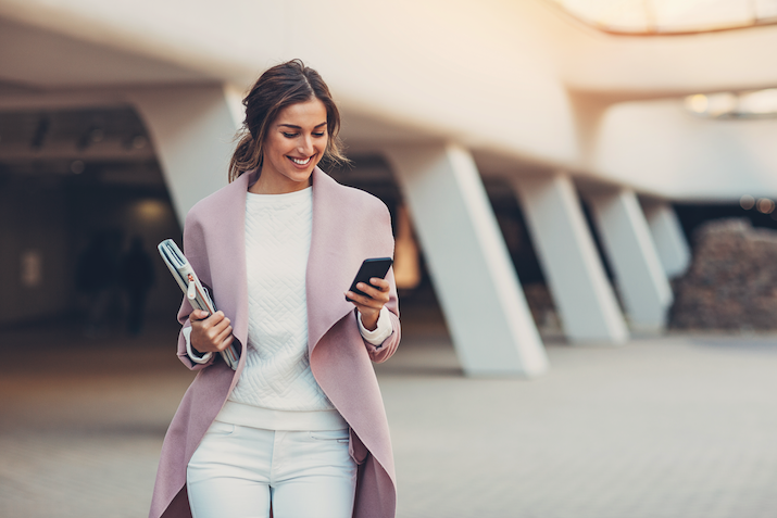woman walking with a notebook and phone