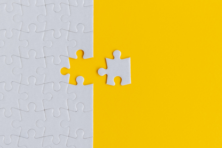A white puzzle with one piece missing on a yellow background, the white piece lies to the right on the yellow background